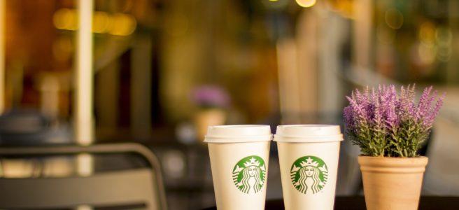 Genießen Sie Ihr Heißgetränk im Starbucks Thermobecher - Eine Tasse Kaffee und eine Blumenvase auf einem Tisch - Cafe