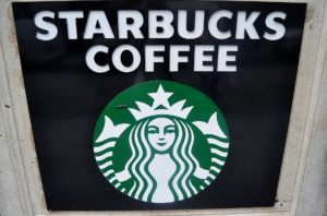 Genießen Sie Ihr Heißgetränk im Starbucks Thermobecher - Ein schwarzes Schild mit weißer Schrift - Starbucks